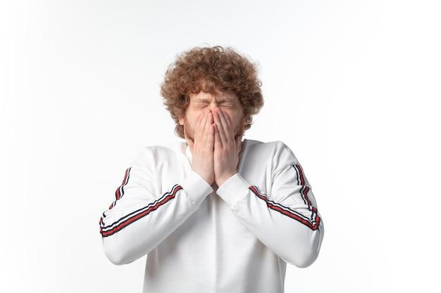 Eerste symptomen. man hoesten, gezicht verbergen op witte muur.