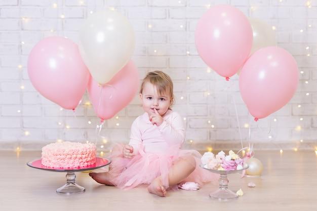 Eerste verjaardag schattig klein meisje taart eten over bakstenen muur achtergrond met lichten en ballonnen