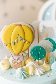 Eerste verjaardagstaart voor kinderen, blauwe cake met wolken, meringue en ballonnen