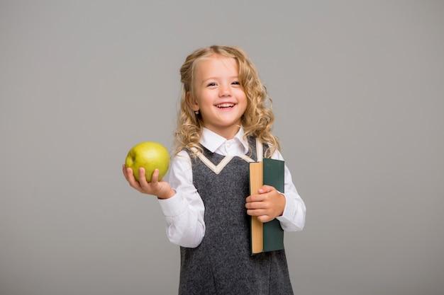 Eersteklasser met boeken en een appel lachend op een lichte achtergrond
