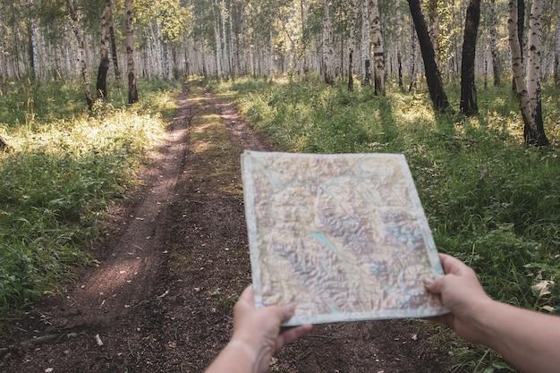 Eerstepersoonsperspectief met twee handen, de kaart voor zich houden en verderop is een bosweg