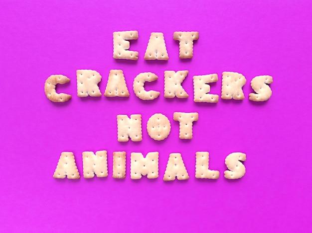 Eet crackers, geen dieren. voedsel typografie op roze achtergrond. veganistisch concept.