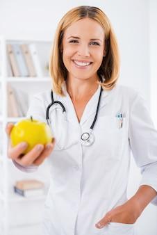Eet gezond! vrolijke vrouwelijke arts in wit uniform die de hand uitstrekt met groene appel