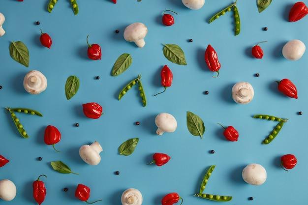 Eetbare gezonde voedingsgroenten op blauwe achtergrond. witte champignons, groene erwten, rode peper en peperkorrels kunnen worden toegevoegd om een heerlijk gerecht te bereiden. ingrediënten voor champignoncurry of roomsoep