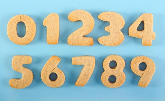 Eetbare handgemaakte nummers cookies op blauwe achtergrond