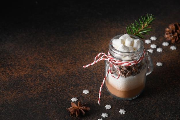 Eetbare kerstcadeau in glazen pot cadeau voor het koken van warme chocolademelk op bruin. detailopname.