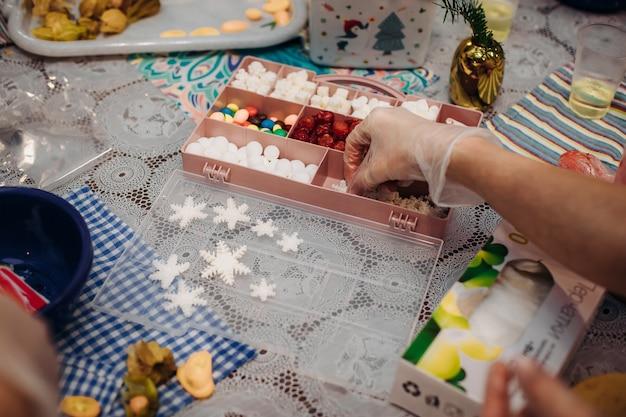 Eetbare kerstversieringen, voor taartdecoratie. handen van de patissier close-up. kerst vakantiesfeer. werkomgeving. creatieve puinhoop