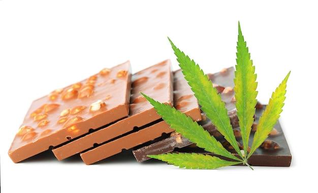Eetbare medische marihuanavoedsel chocoladerepen en chocoladekoekjes met groen hennepblad geïsoleerd