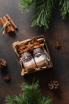 Eetbare twee kerstcadeaus van koekjes en glazen pot voor het maken van chocoladedrank