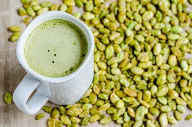 Eetbare zaden van hyacint bonensnack en groene thee latte op hout
