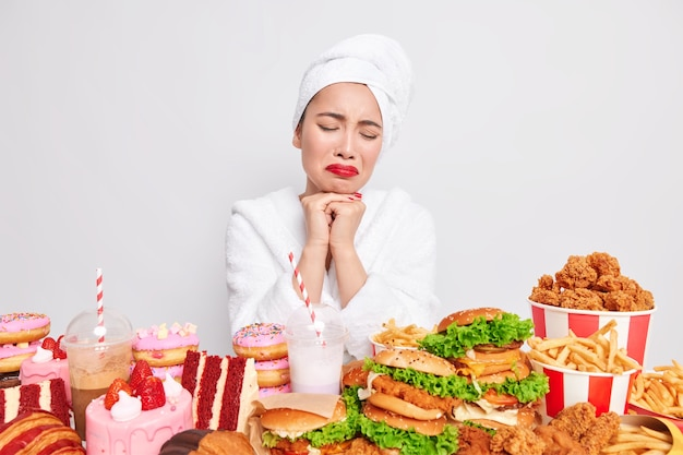 Eetbuien concept. gestresste ongelukkige aziatische dame wil fastfood eten