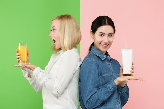 Eetpatroon. dieet concept. gezond eten. mooie jonge vrouwen die kiezen tussen sinaasappelsap en een onheldere, koolzuurhoudende zoete drank