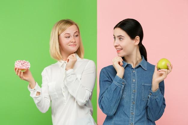 Eetpatroon. dieet concept. gezond eten. mooie jonge vrouwen kiezen tussen fruit en onheilspellende cake