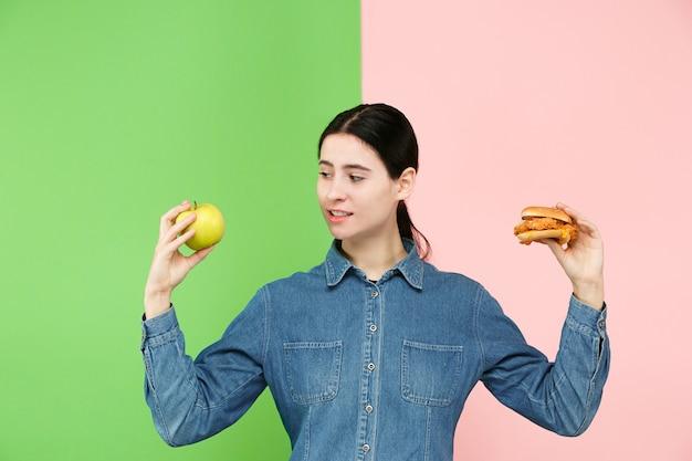 Eetpatroon. dieet concept. gezond nuttig voedsel. mooie jonge vrouw die tussen vruchten kiest