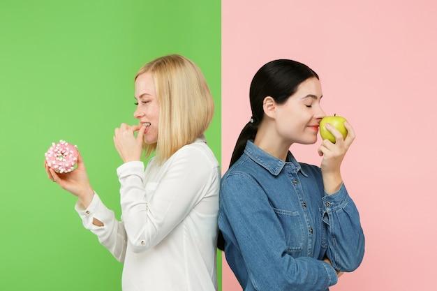 Eetpatroon. dieet concept. gezond, nuttig voedsel. mooie jonge vrouwen die tussen fruit en unhelathy cake bij studio kiezen. menselijke emoties en vergelijkingsconcepten