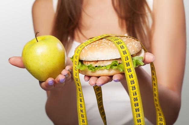 Eetpatroon. schadelijk en nuttig voedsel. een jong meisje maakt een keuze voor een dieet of voor een maaltijd. sport. het concept van gezondheid en schoonheid. op een grijze achtergrond.