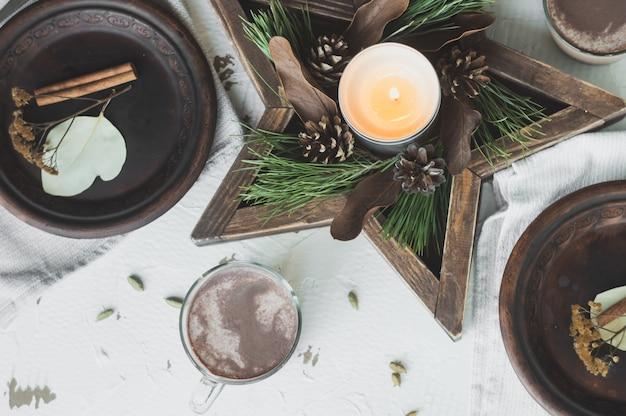 Eetplaats versierd met dennenappels, takken en gouden kerstversiering
