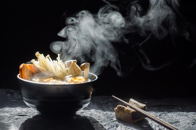 Eetstokjes aan smakelijke noedels met stoom en rook in kom op donkere achtergrond
