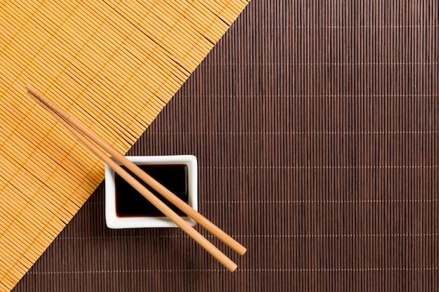Eetstokjes en kom met sojasaus op twee bamboe mat blak en geel bovenaanzicht met kopie ruimte
