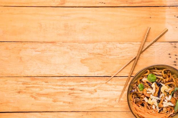 Eetstokjes en kom udonnoedels garneren met garnalen; noten; kruiden en garnalen over de tafel