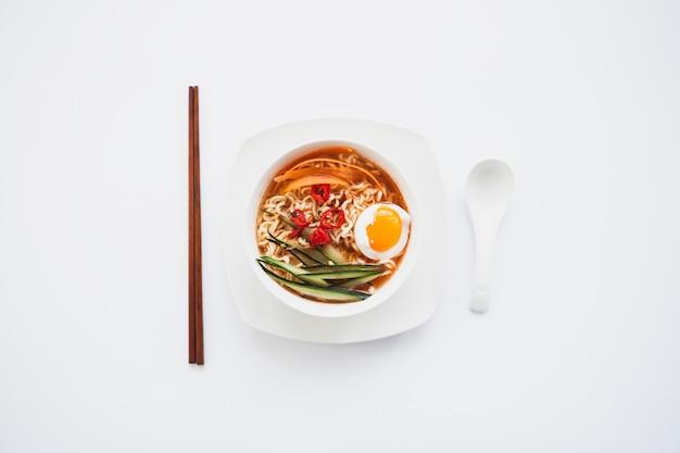 Eetstokjes en lepel dichtbij aziatische soop