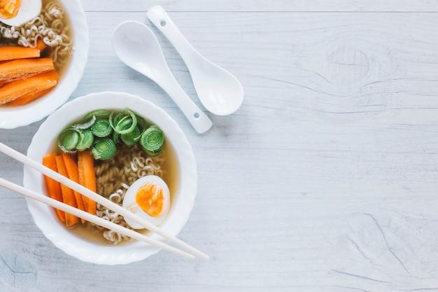 Eetstokjes en lepels in de buurt van noodle soupe
