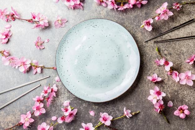 Eetstokjes en sakura-takken op grijze steen
