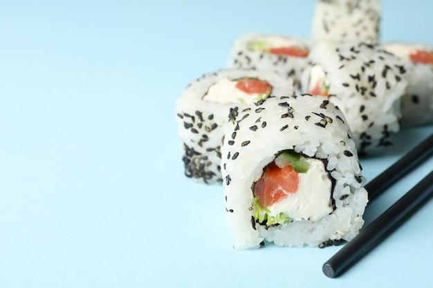 Eetstokjes en sushi rolt op blauwe ondergrond. japans eten