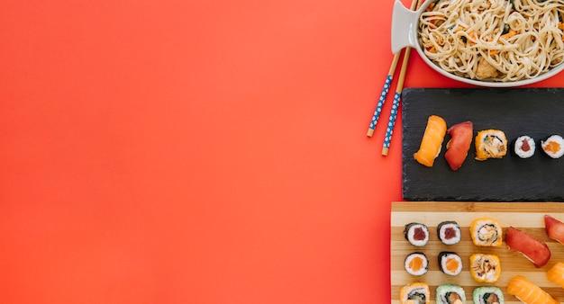 Eetstokjes in de buurt van noedels en sushi op rood