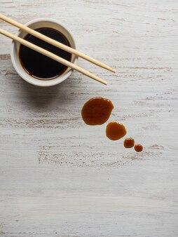 Eetstokjes met lekkende sojasaus op de houten tafel