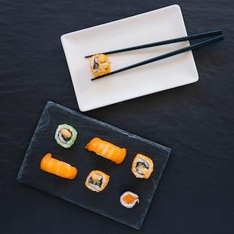 Eetstokjes met roll in de buurt van sushi