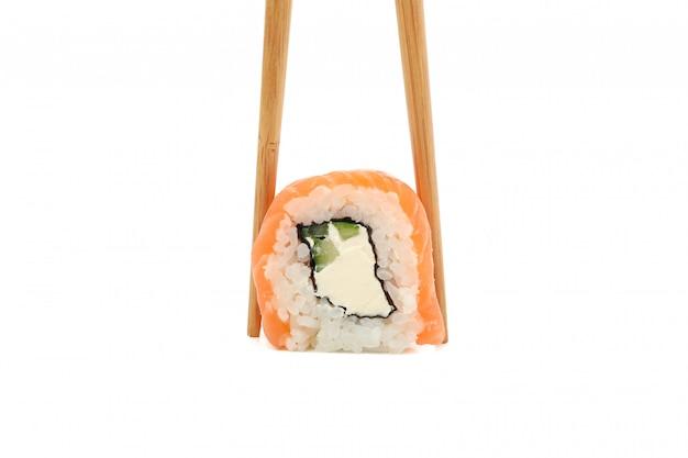 Eetstokjes met sushi roll geïsoleerd op een witte ondergrond