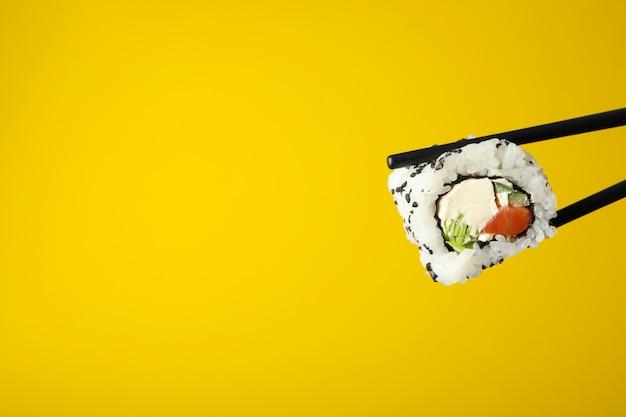 Eetstokjes met sushi roll op gele ondergrond. japans eten