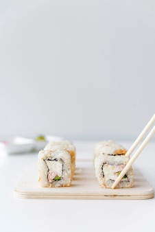 Eetstokjes oppakken van sushi roll