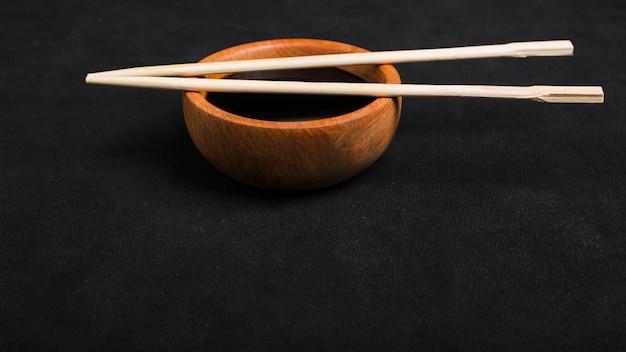 Eetstokjes over de houten kom van de sojasaus op zwarte achtergrond