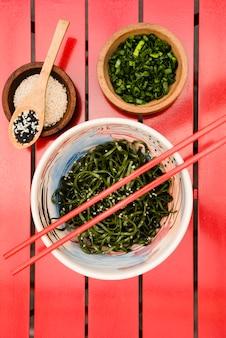 Eetstokjes over de japanse chuka zeewier salade geserveerd met sesamzaadjes en gehakte lente-uitjes op rode tafel