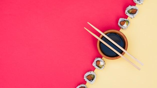 Eetstokjes over de sojasauskom met sushi op gele en rode dubbele achtergrond