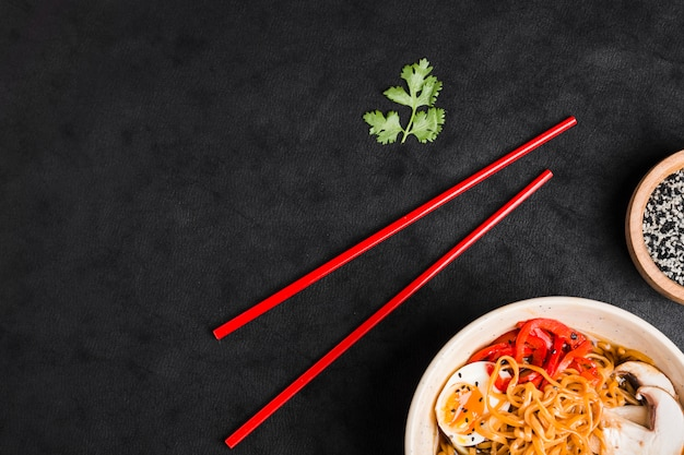 Eetstokjes; peterselieblad en kom noedels met ei; paddenstoelen en paprika's