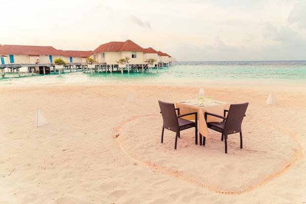 Eettafel en stoel op het strand met uitzicht op zee achtergrond in de maldiven