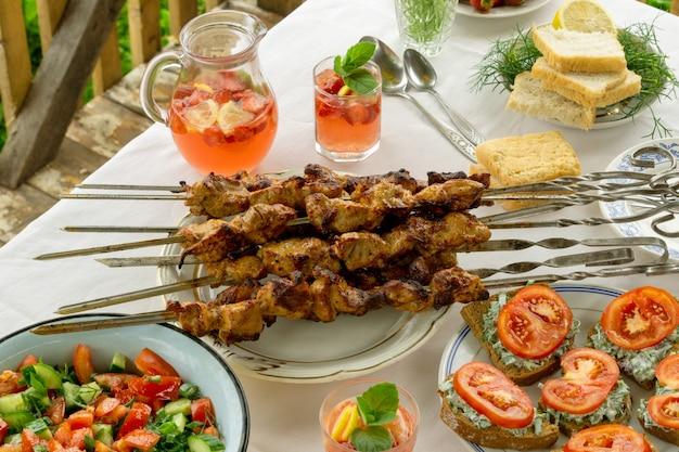 Eettafel met barbecue, snacks en aardbeienlimonade