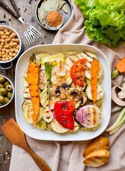 Eettafel met diverse gegrilde groenten brood en snacks op houten oppervlak