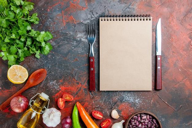 Eettafel met een bos van groene knoflook van de oliefles en notitieboekje op gemengde kleurentafel
