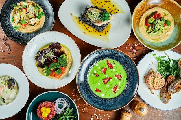 Eettafel met een heleboel voedsel. groene roomsoep, hummus, dorado, paté, bouillabaisse en rundertartaar voor een familiediner. bovenaanzicht eten plat lag.