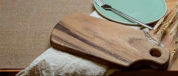 Eettafel met mock-up houten dienblad, keramische plaat, zilveren vork, servet en kopie ruimte op placemat