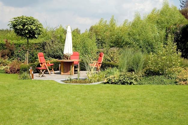 Eettafel met stoelen en parasol in een weelderige tuin