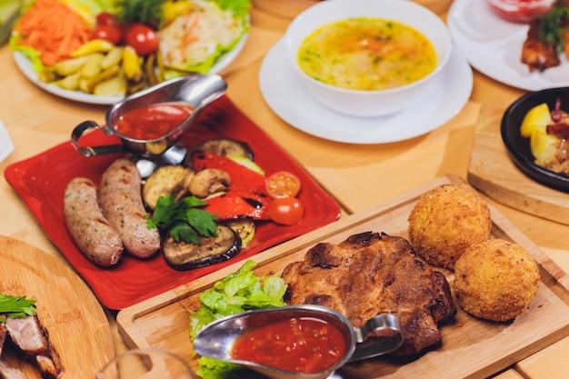 Eettafel met verschillende snacks en salades. zalm, olijven, wijn, groenten, gegrilde vis toast. het concept van een familiefeestdiner.