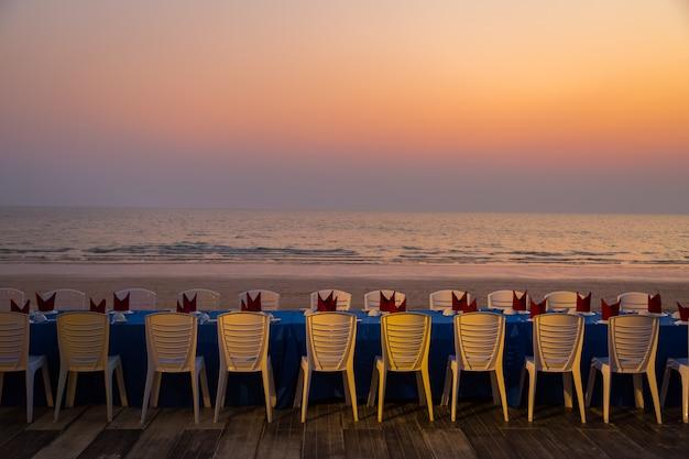 Eettafel op het strand tijdens zonsondergang achtergrond