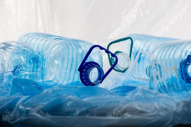 Eeuwen van ontbinding. stapel heldere waterstokken die worden geleegd en wachten op recycling met stukjes verkruimeld materiaal