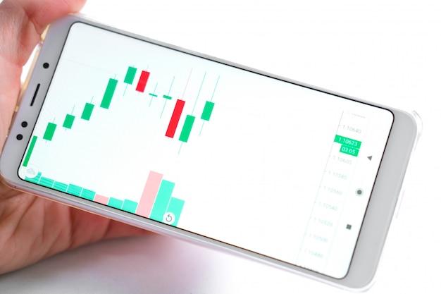 Effectenbeursgrafiek op mobiel apparaat in de hand van de zakenman