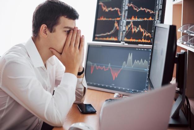 Effectenmakelaar in overhemd werkt in een controlekamer met beeldschermen. beurs handel forex financiën grafisch concept. zakenlieden die online voorraden verhandelen.